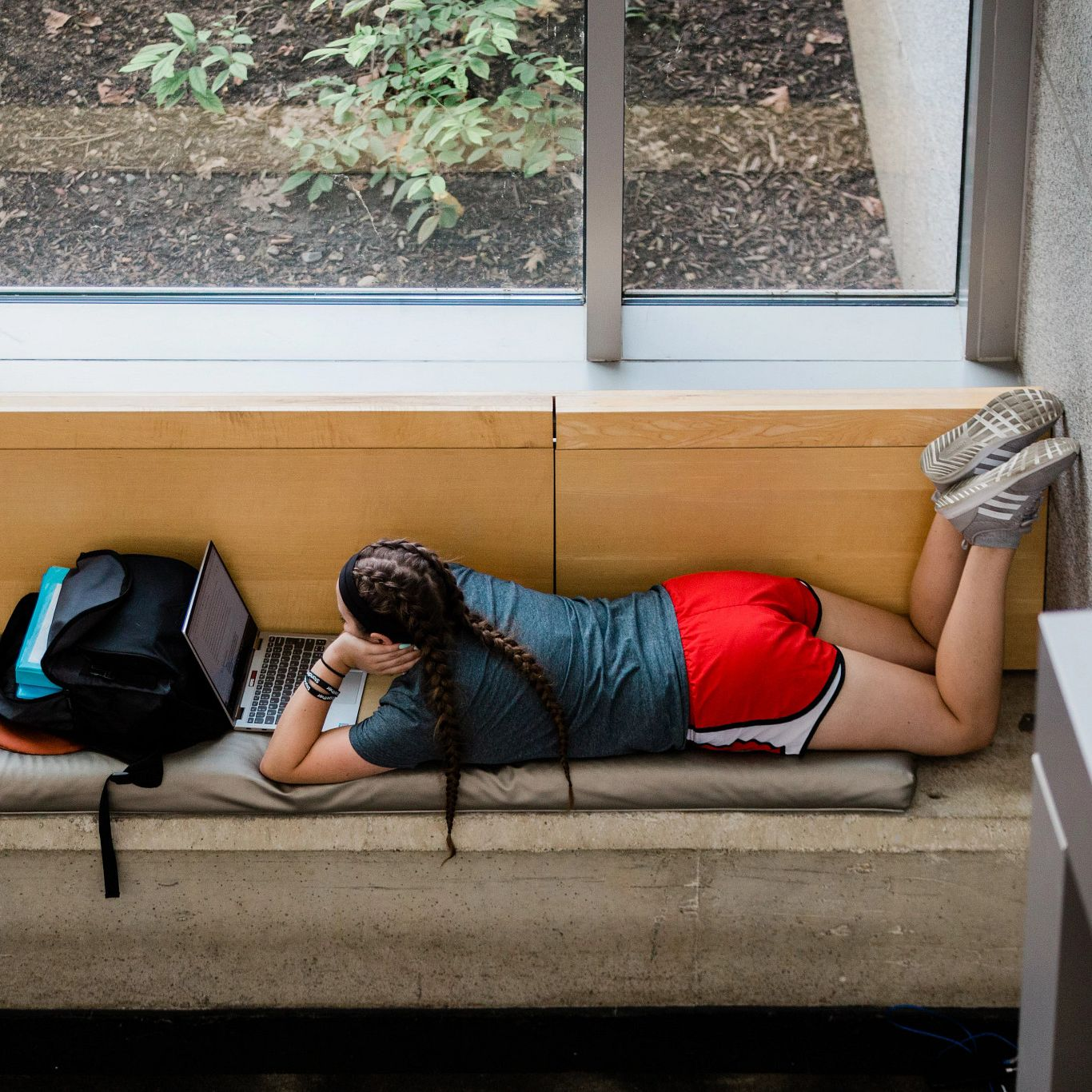 Student lying on a couch looks at her laptop