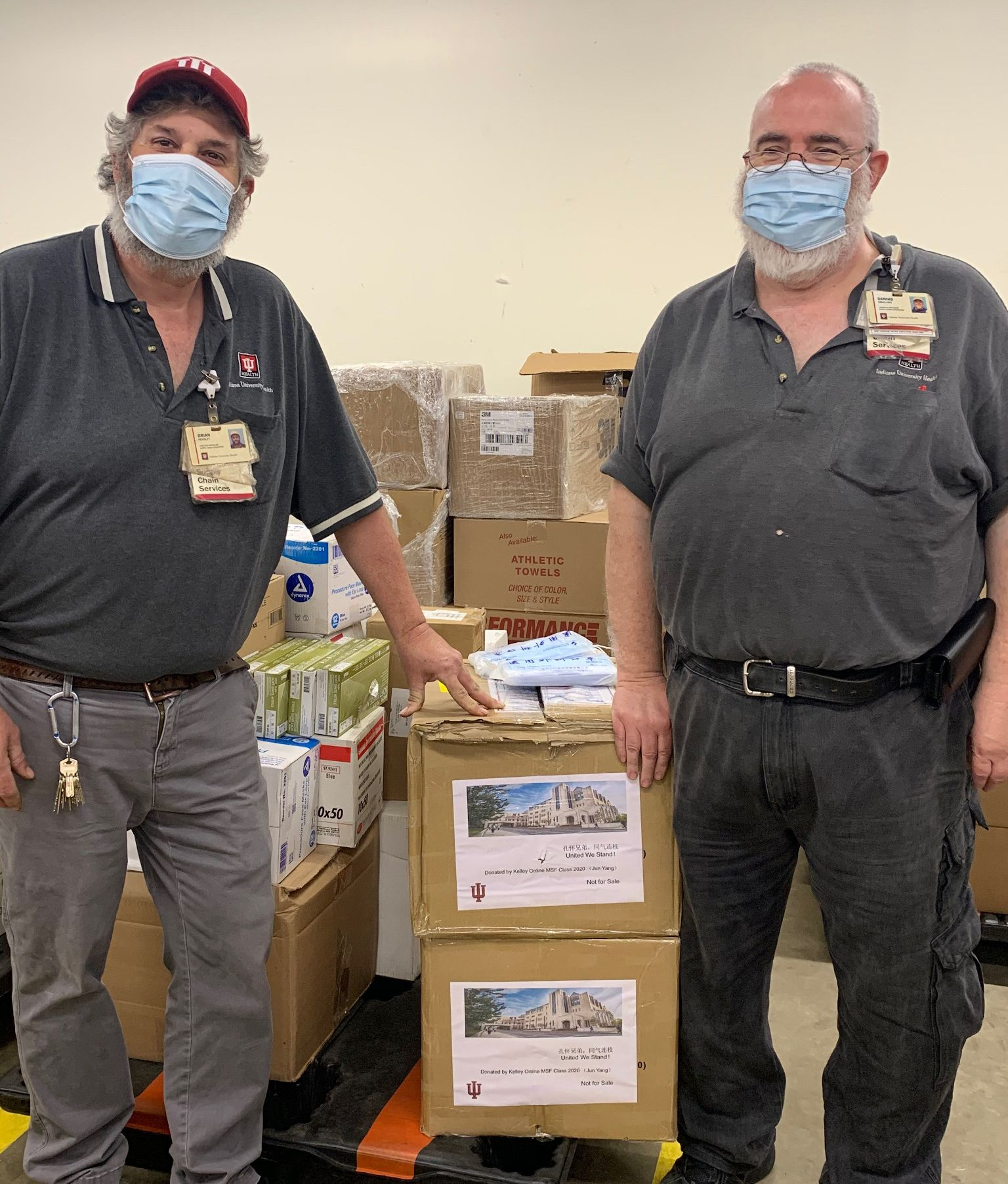 Two men standing with a box of donated items