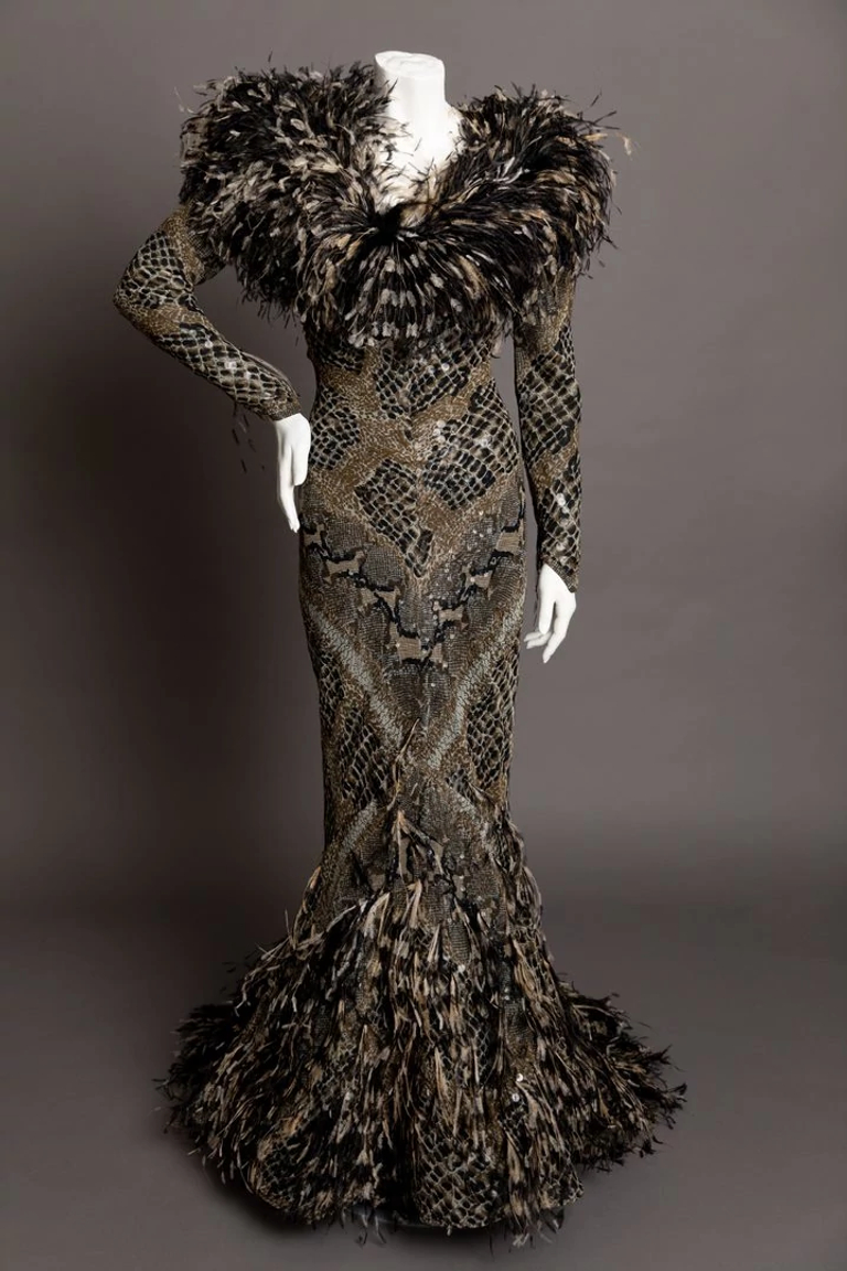 Mannequin in a body-hugging chiffon snake-print dress with feathers on the neckline and hem