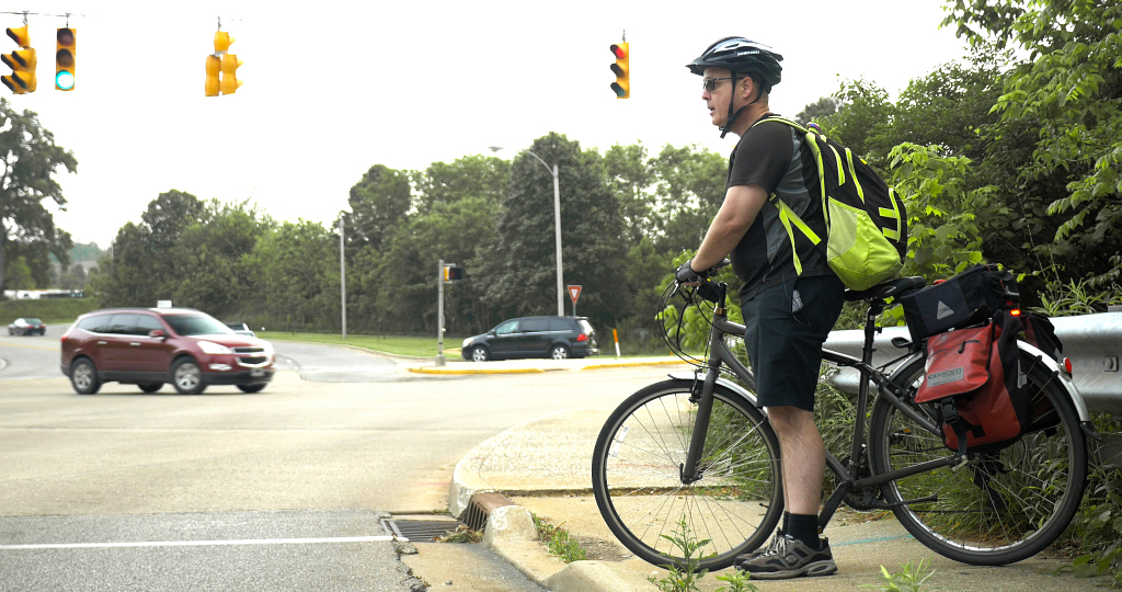 A man on his bicycle, waiting for a stoplight to change on a curb