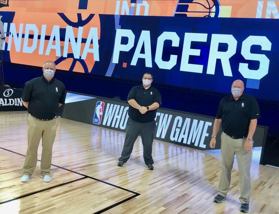 three people wearing masks standing on a basketball court
