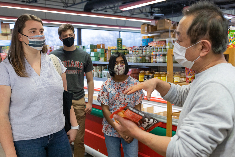 Grocery store owner talks with students