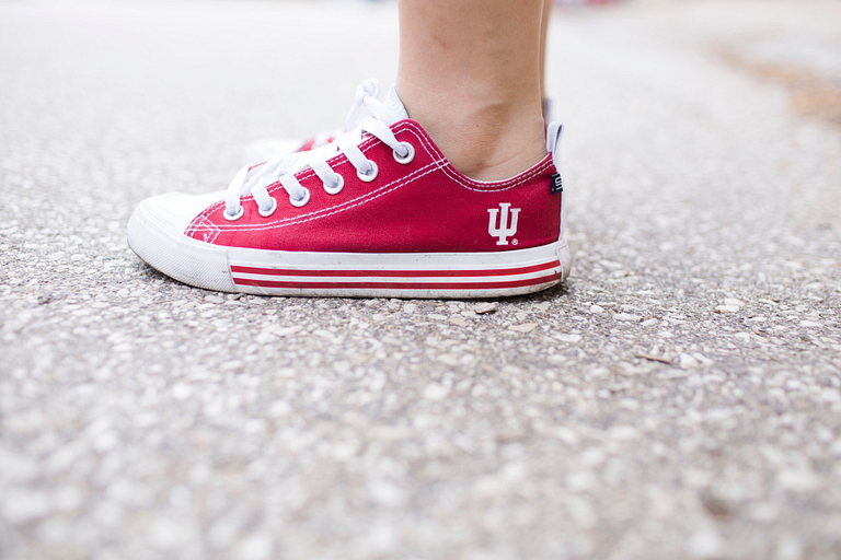 A person wearing a red shoe with an IU trident on it