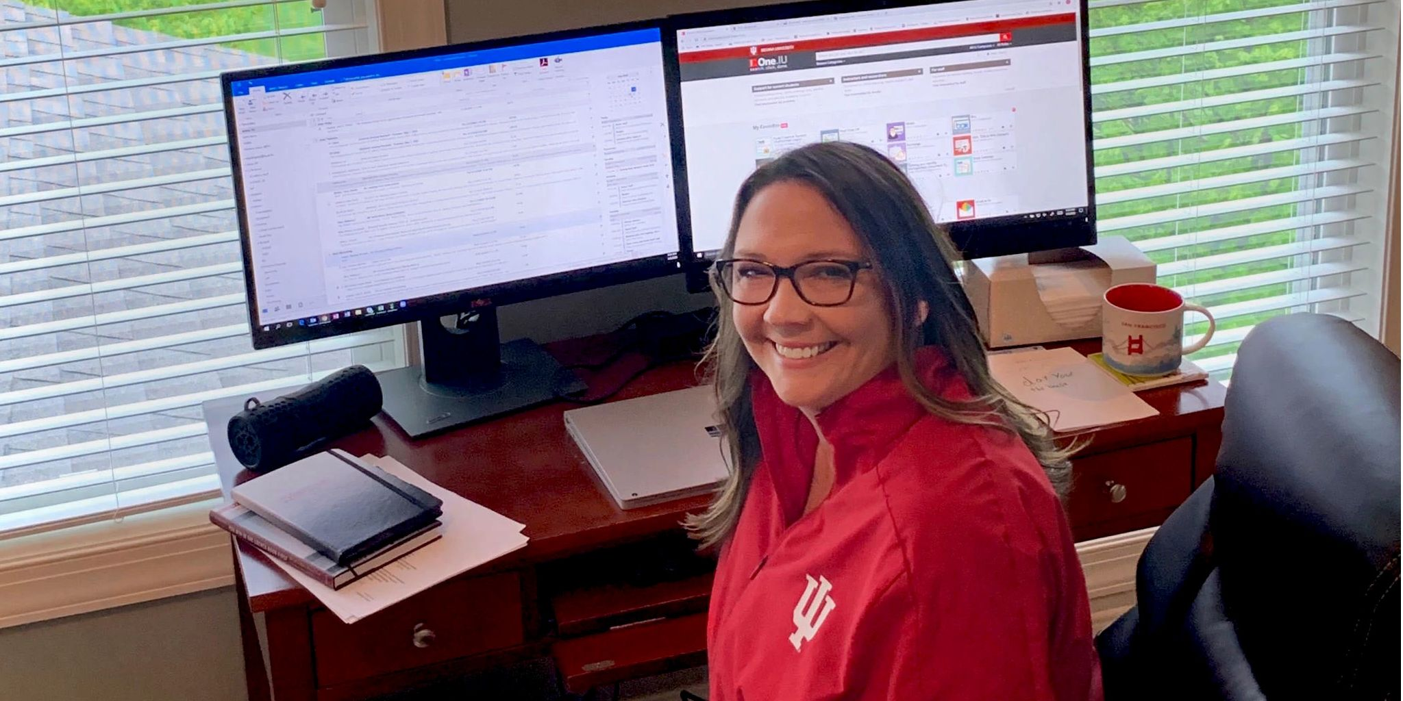 A woman wearing a red IU jacket sits at a computer desk in her home.