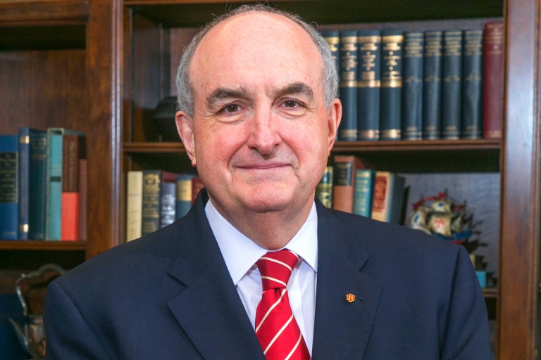 IU President Michael A. McRobbie is pictured in front of a bookcase