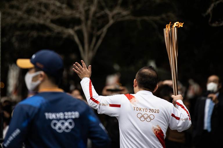 A relay runner carries the Olympic torch through a crowd