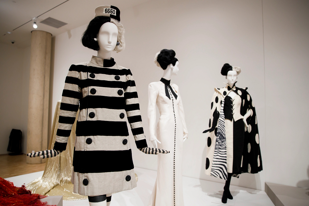 A striped prison costume is pictured next to two other black and white costumes