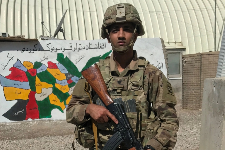 Arsalan Rehman in combat gear holding a rifle