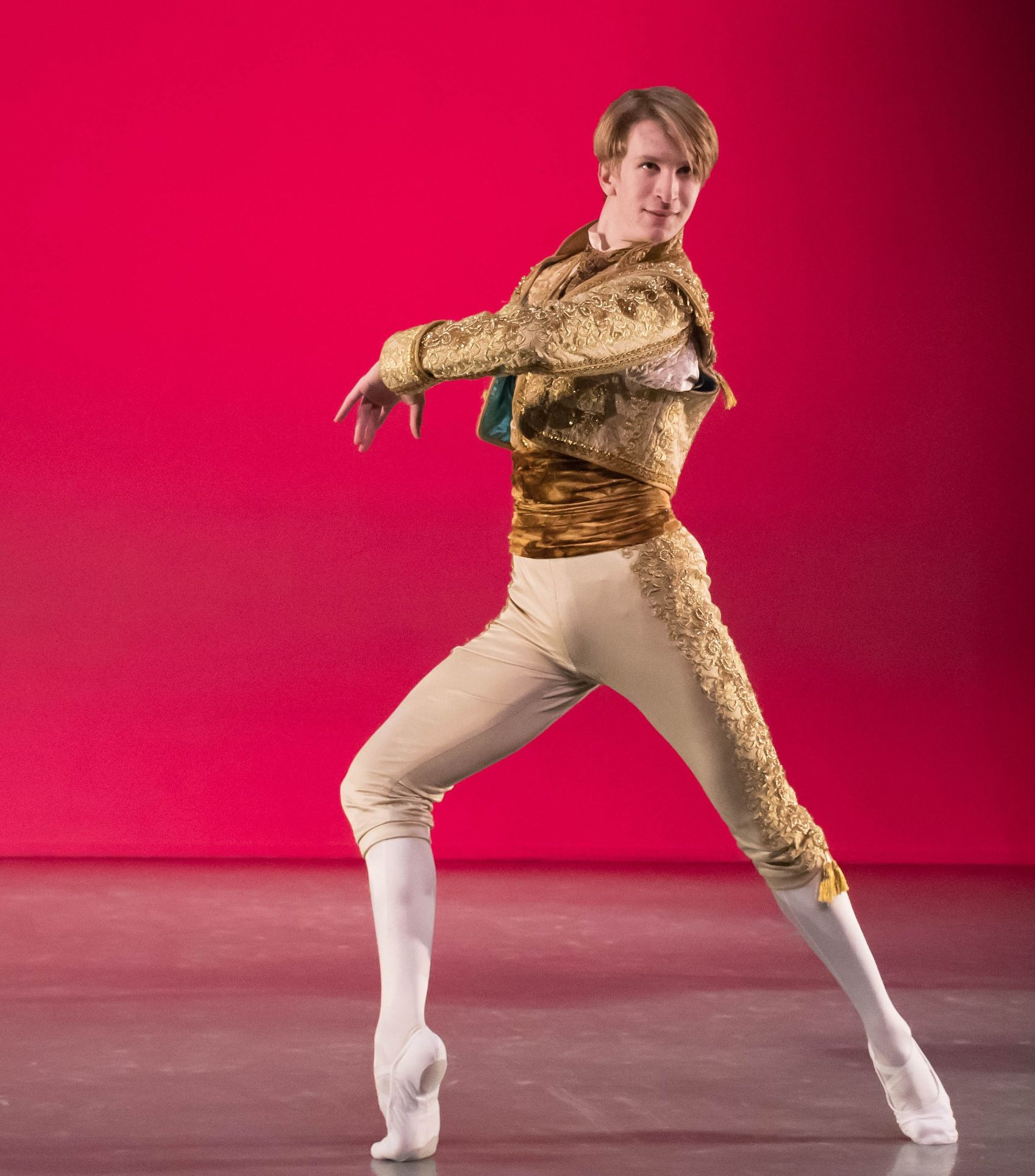 A male ballet dancer performs on stage
