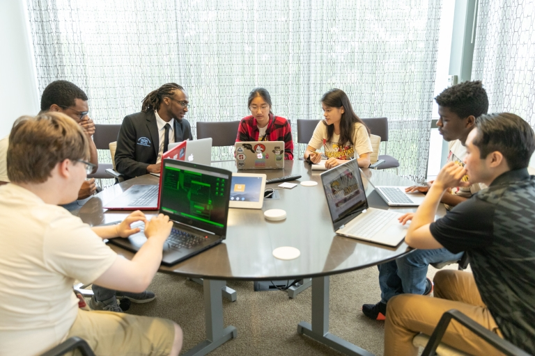 A group of seven students seated at a round table, studying with laptops