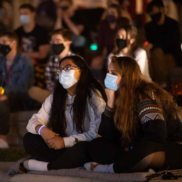Two female students watch screen while wearing face masks