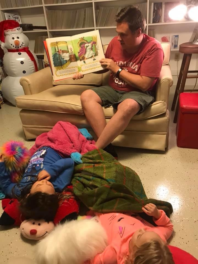 Trent Deckard reading to his daughters