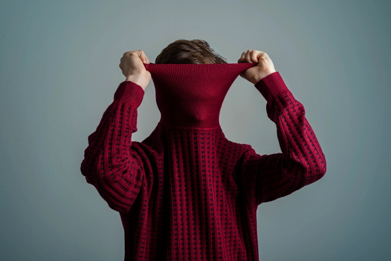 a person pulling a red sweater over their head