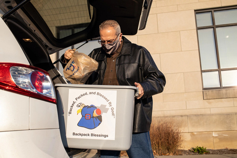 IU staff member Chuck Aikman takes food items from his vehicle
