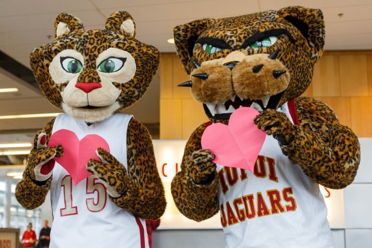 IUPUI jaguar mascots Jazzy and Jaws hold paper hearts