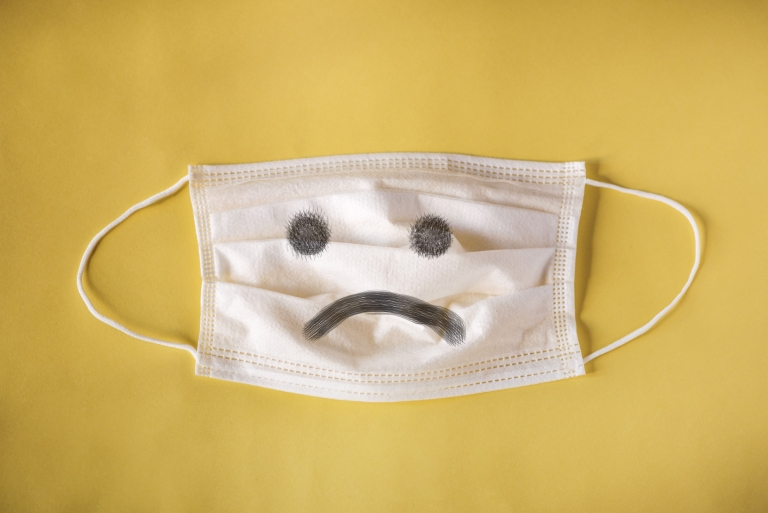 Yellow image with white surgical mask in center that has a sad face drawn onto it.