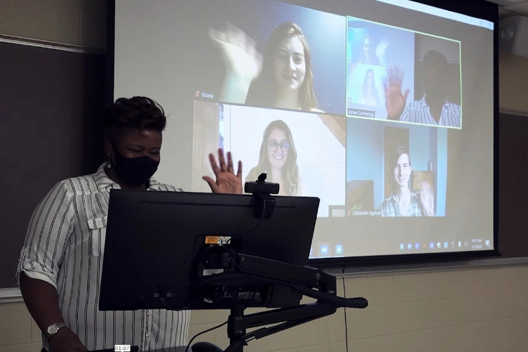 A teacher wearing a mask in a classroom waves to students seen on projector screen.