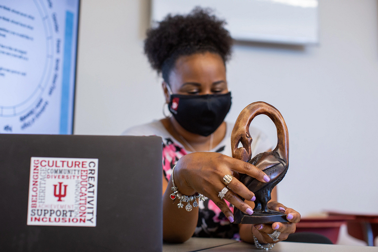 A Black professor holding a sculpture while sitting at a desk in front of a laptop