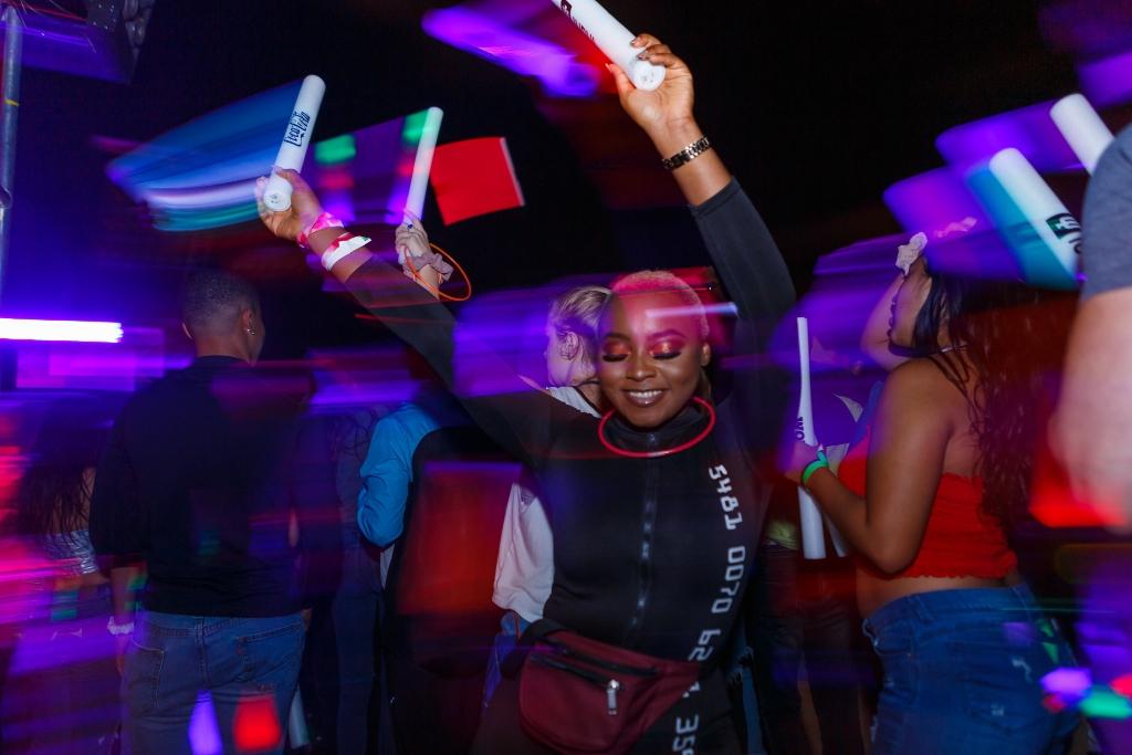 A woman dances with neon batons