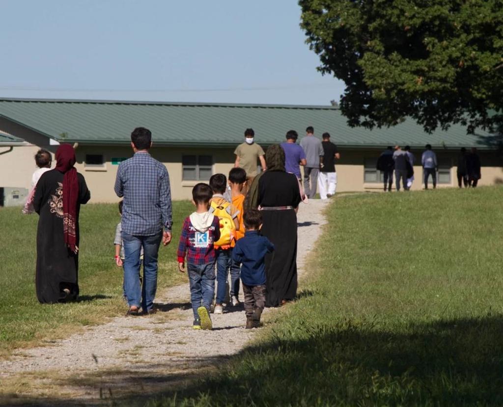 Afghan refugees walking at Camp Atterbury.