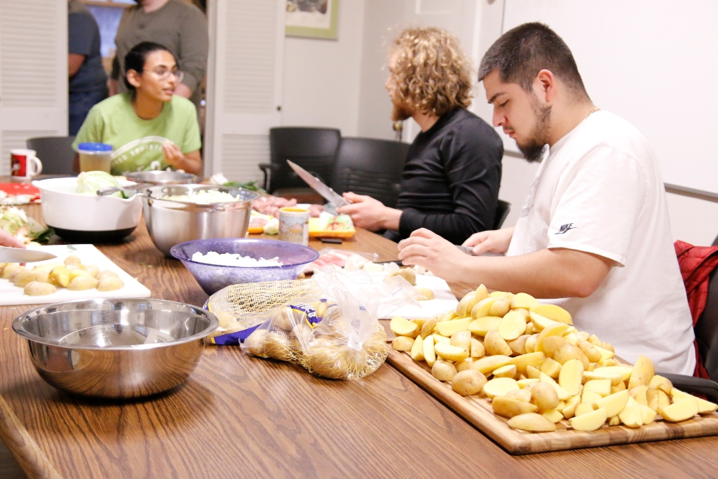 Students sit around a table chopping vegetables