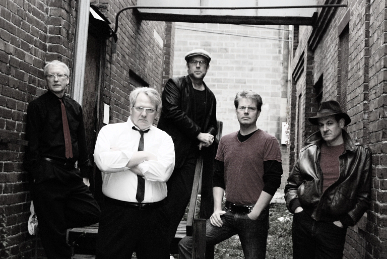 Black-and-white photo of Don't Call Me Betty band members posing in an alley