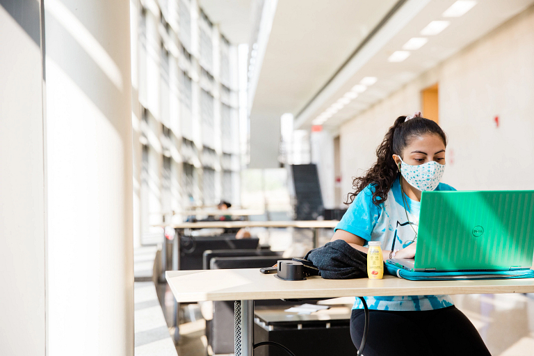 A student wearing a mask sits at a table working on a laptop