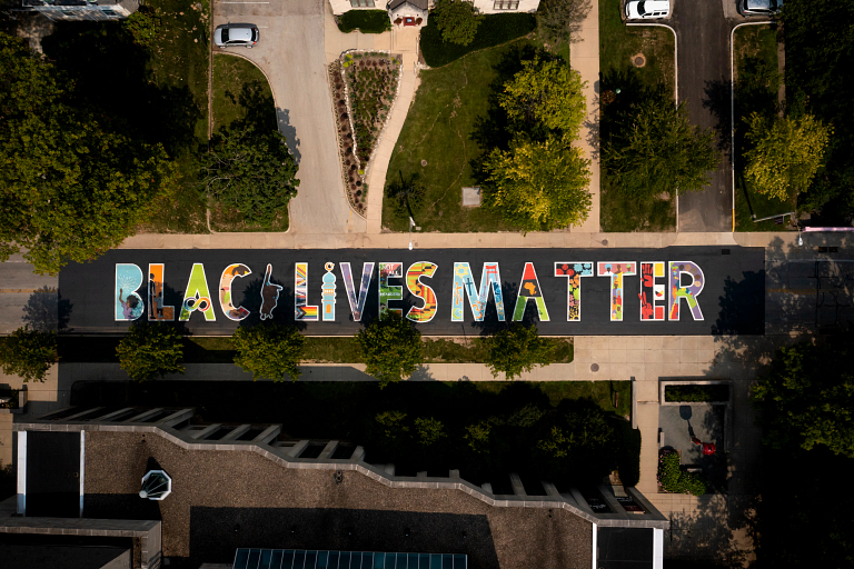 A colorful mural reading 'Black Lives Matter' is displayed on the black pavement of Jordan Avenue
