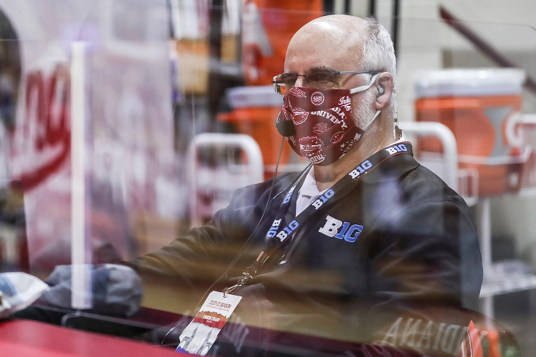 Chuck Crabb wears a mask and is seated behind plexiglass during a game