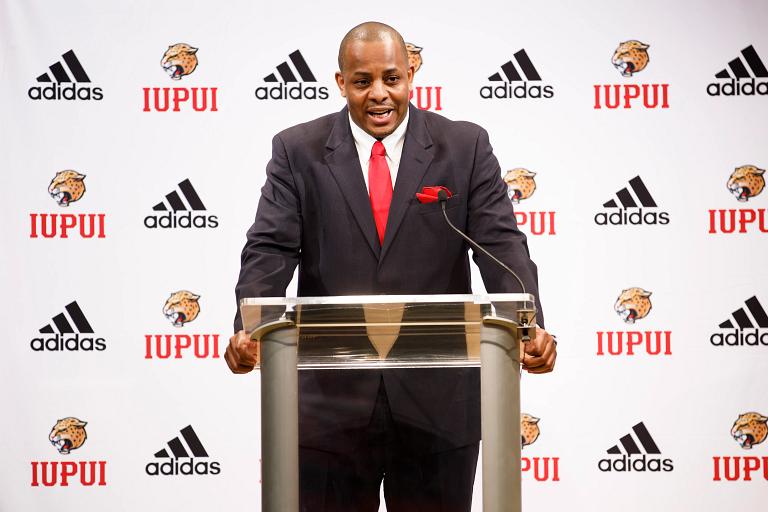 New IUPUI men's basketball coach Matt Crenshaw speaking at a podium.