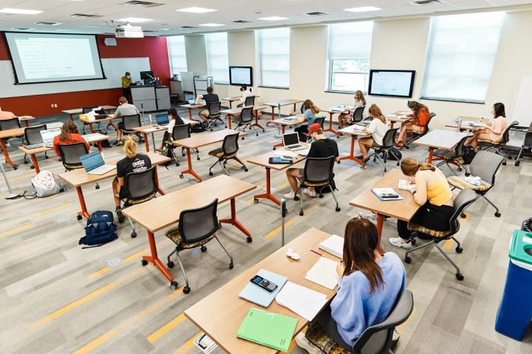 Masked IU students sit at desks