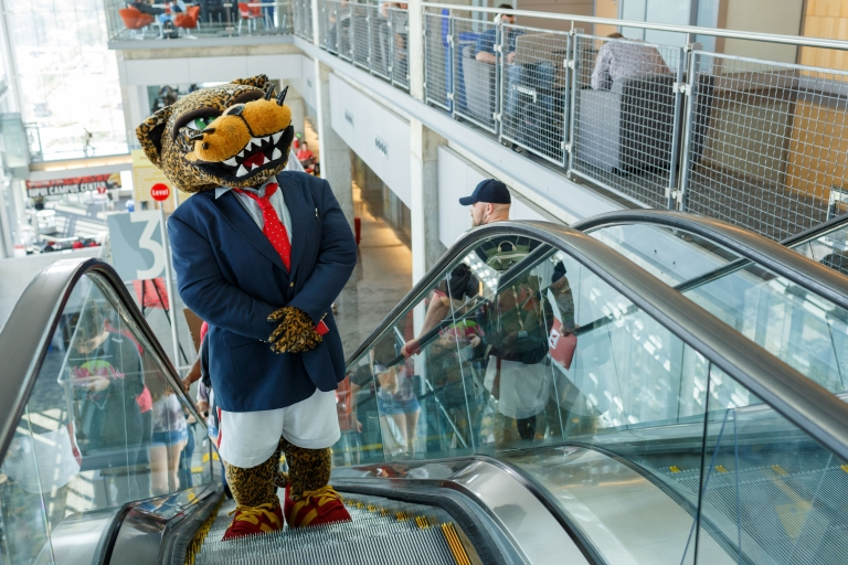 Jawz rides the escalator in the Campus Center to attend the Fall Career Fair.