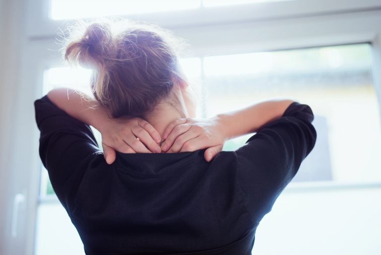 woman grabs behind her head in stress