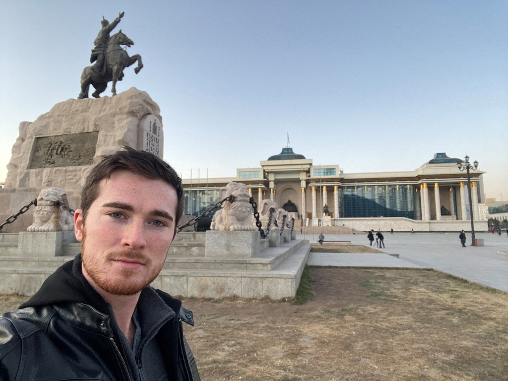 Brandon Boynton standing in front of Mongolia's Government Palace
