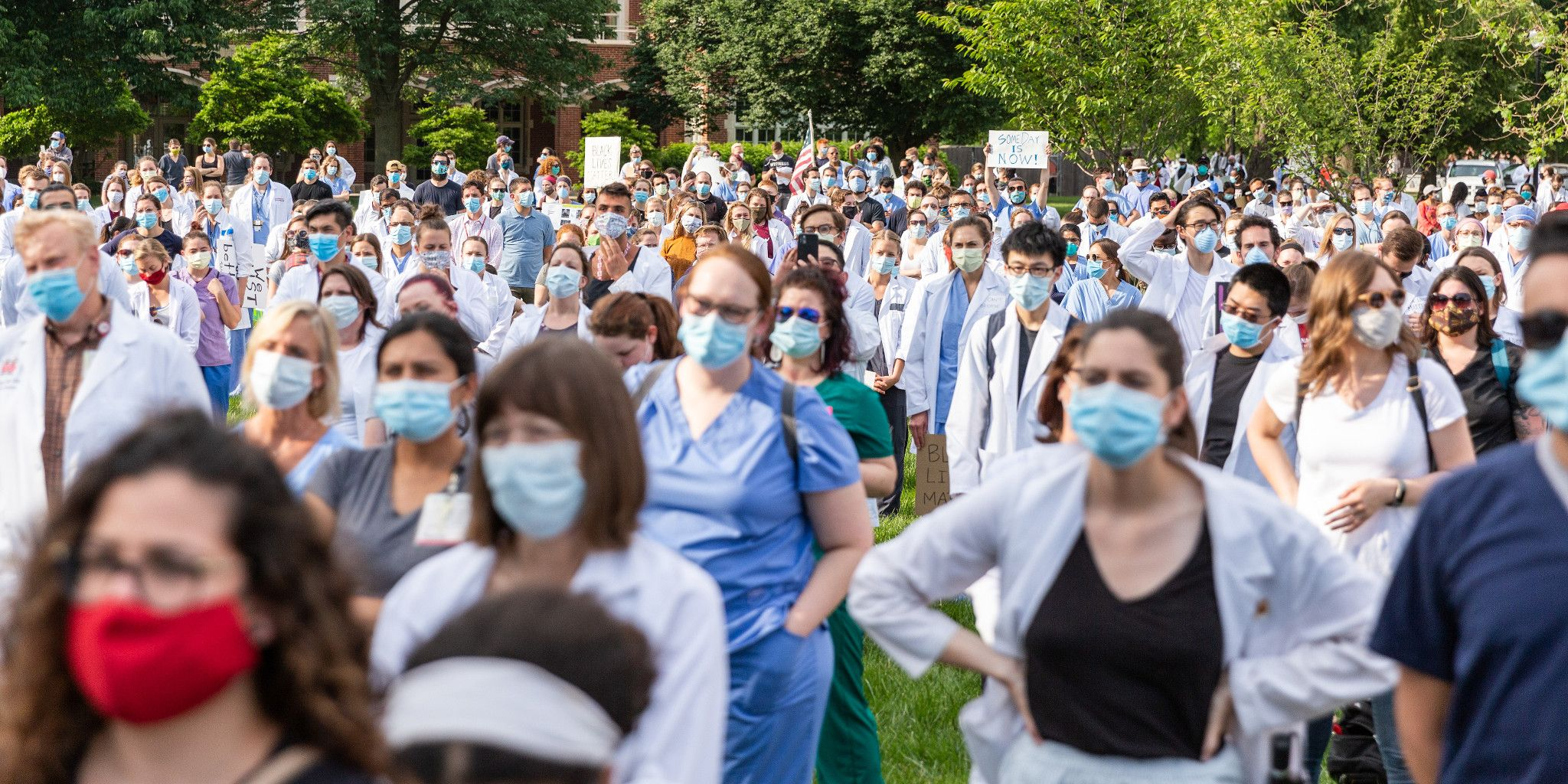A large group of people stand in a grassy area wearing face masks, medical scrubs and coats