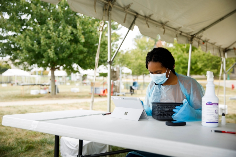 A student in gloves and mask using a tablet computer under a tent outdoors.
