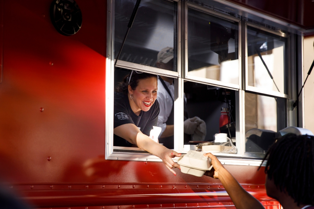 A woman serves food out of a food truck