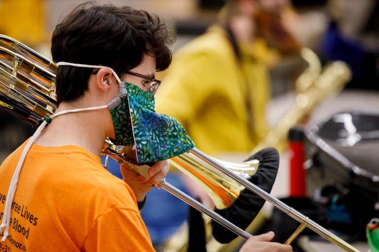 Trombone player wears special instrument face mask