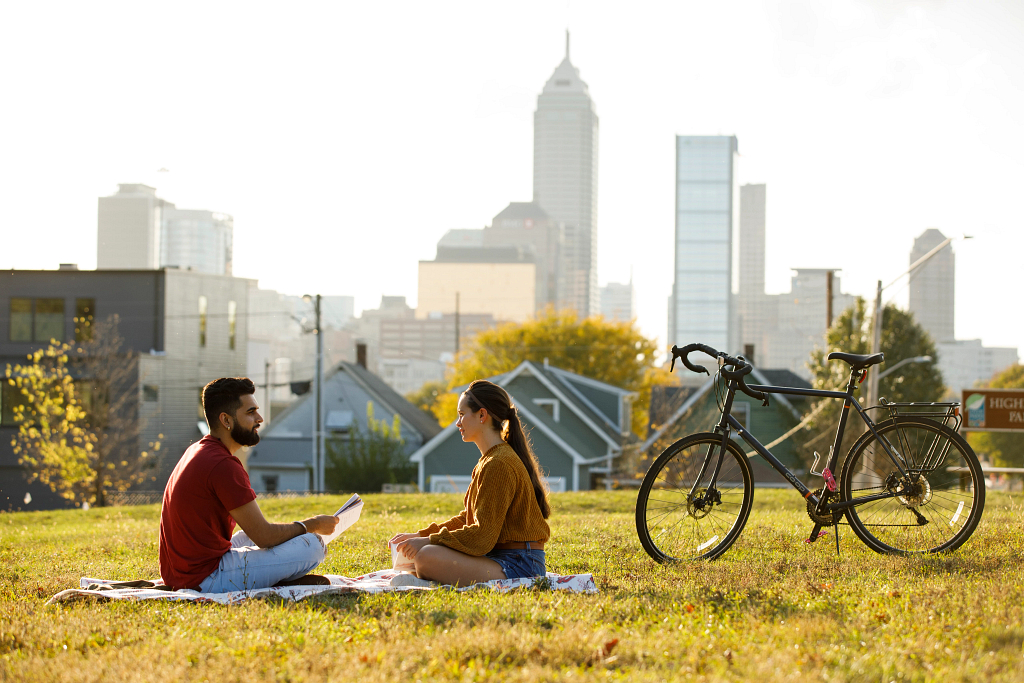 Two students sit in the grass next to a bicycle with Indianapolis skyline in background.