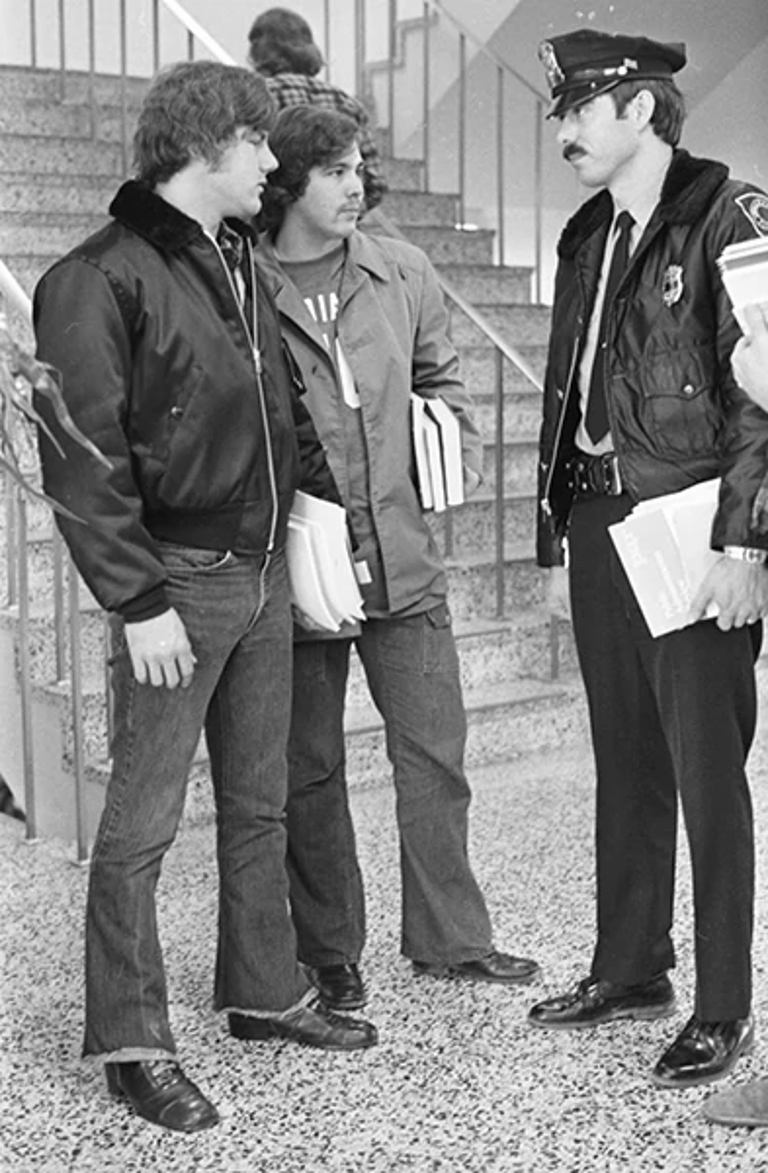 two students and a police officer stand in a black-and-white picture from 1973