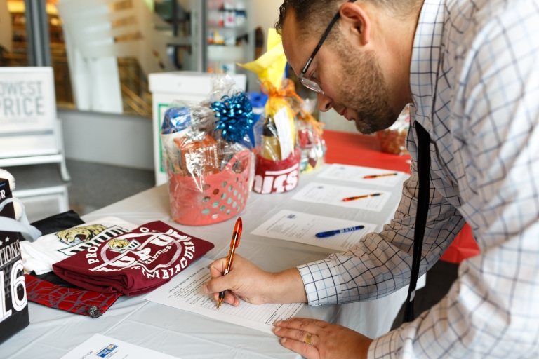 A man signs up at the IUPUI silent auction