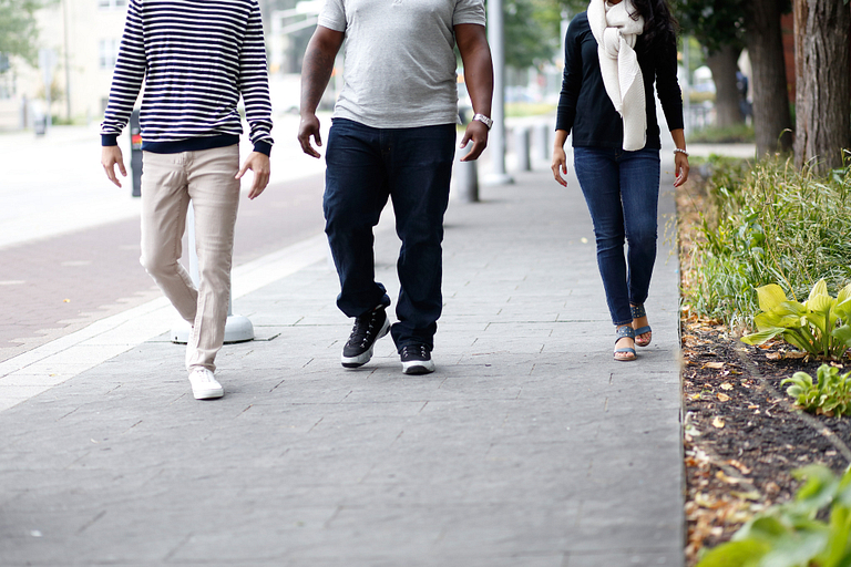 Three people pictured from the torso down walk side-by-side on a pedestrian trail