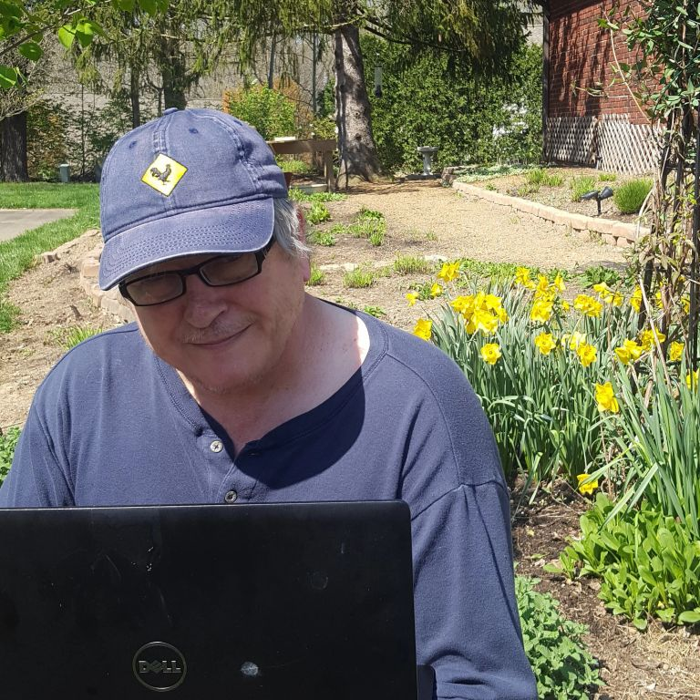 A man works on his laptop while sitting near a garden.