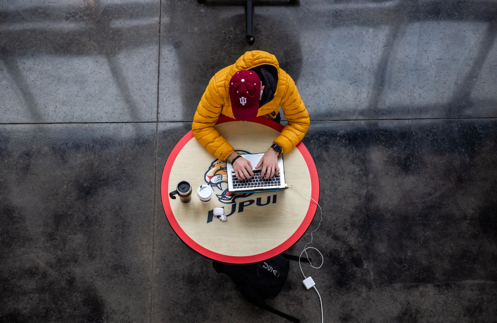 a student studying at a table on the IUPUI campus