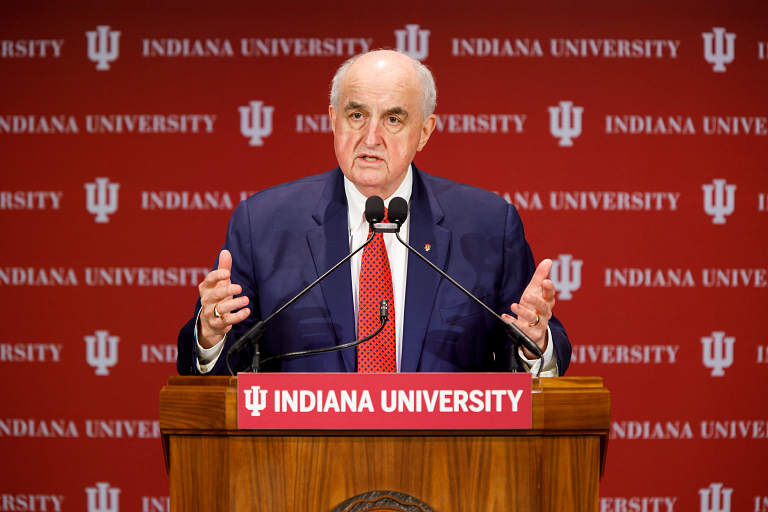 IU President McRobbie speaks at a podium in front of a cream-and-crimson IU background