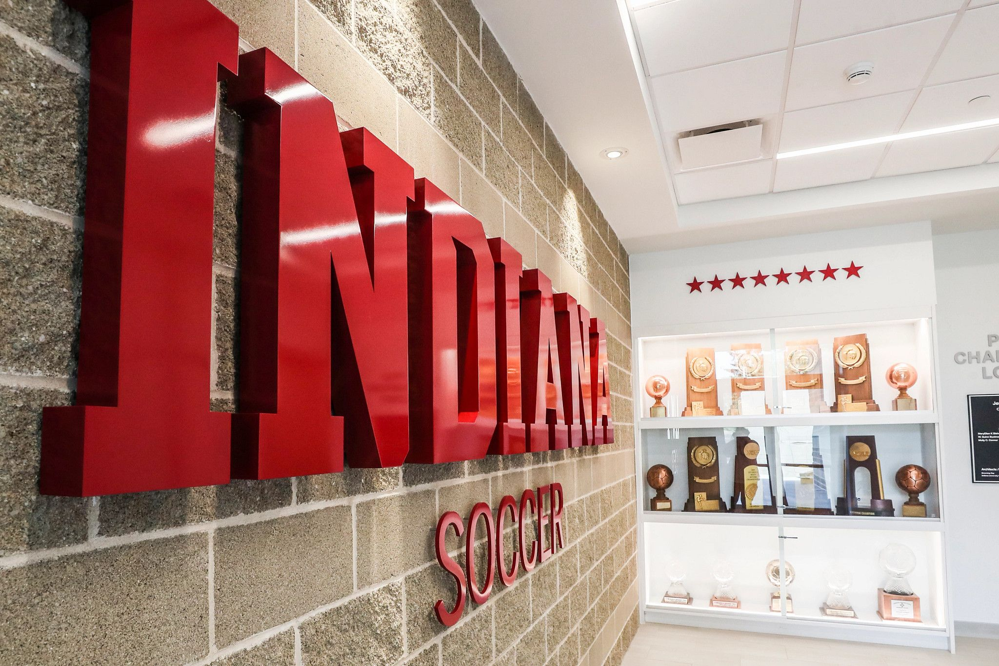 Red letters spelling Indiana soccer hang on a wall next to a trophy case.