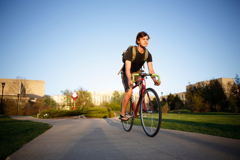 A male student wearing a backpack rides a bicycle along a paved path on a sunny day.