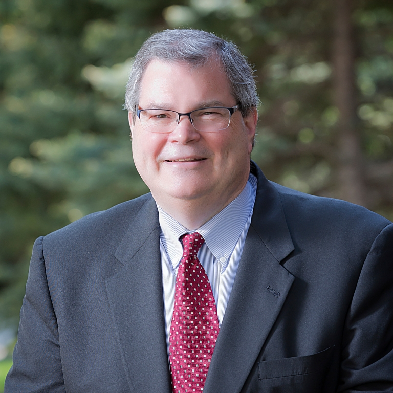A photo of Paul Halverson in a suit and red tie, wearing glasses