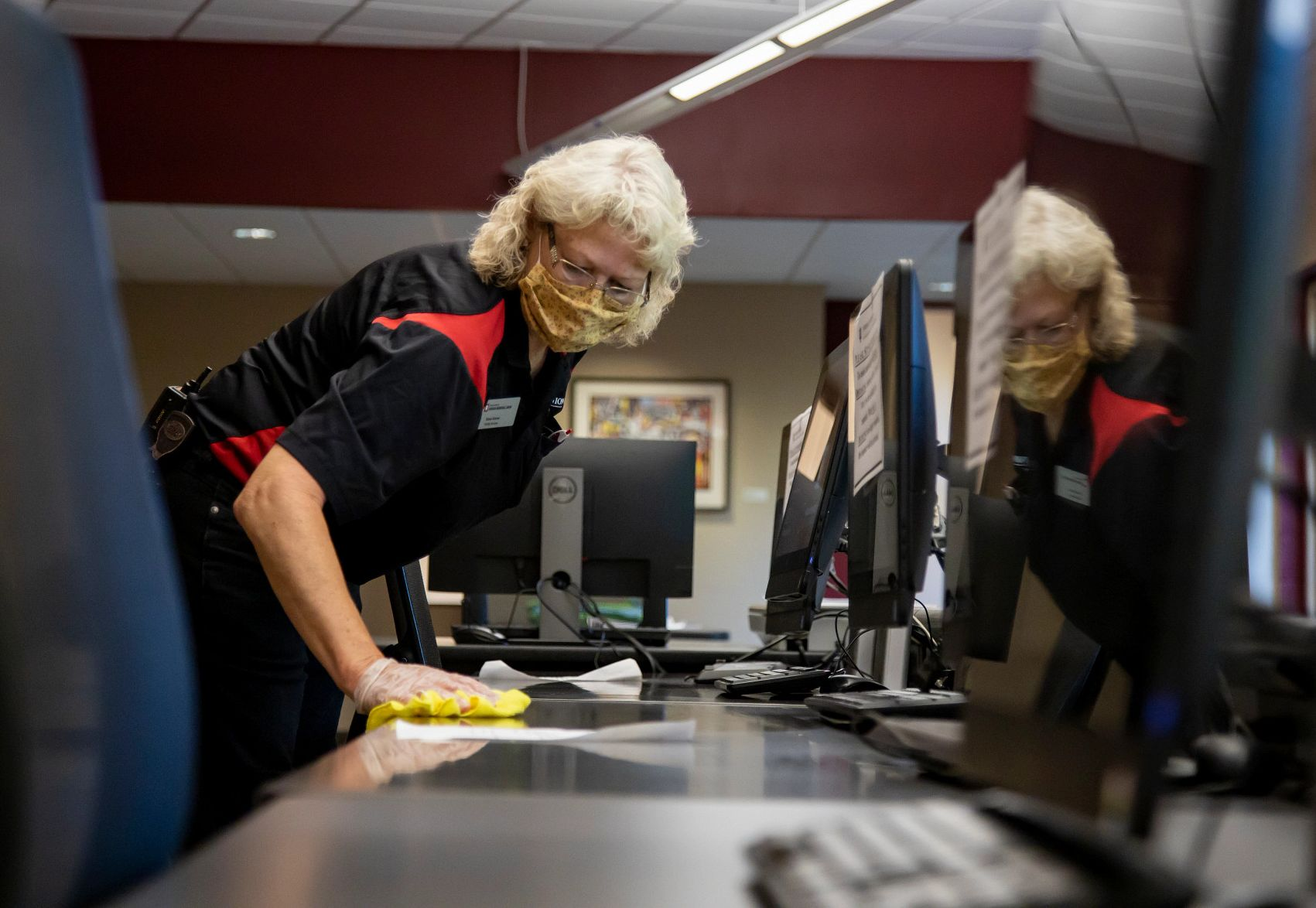 A woman wearing a mask cleans a computer lab table