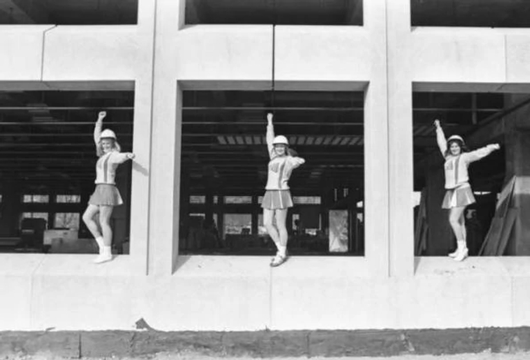 black-and-white image of cheerleaders standing in unfinished windows